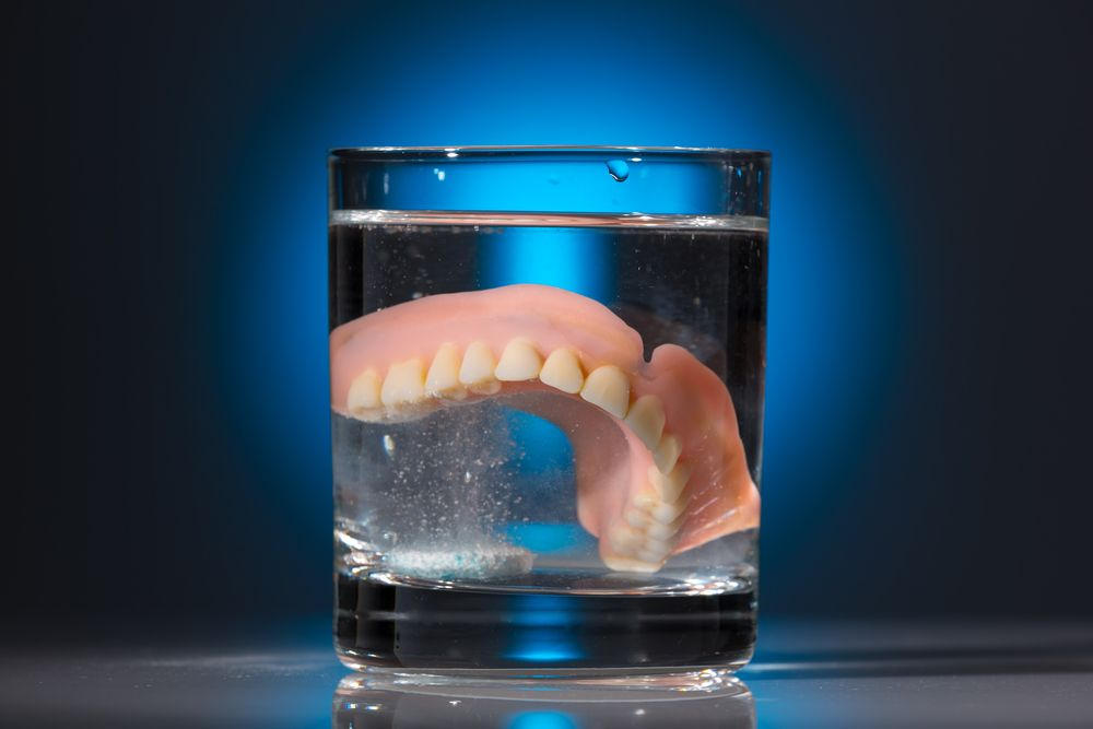 Dentures in a glass of cleaning fluid