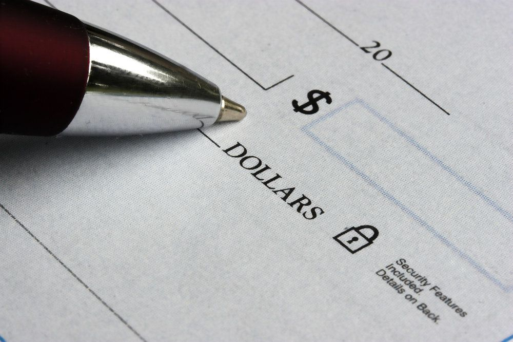 A pen pressed against a blank check