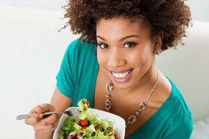 Woman smiling into camera and holding a salad