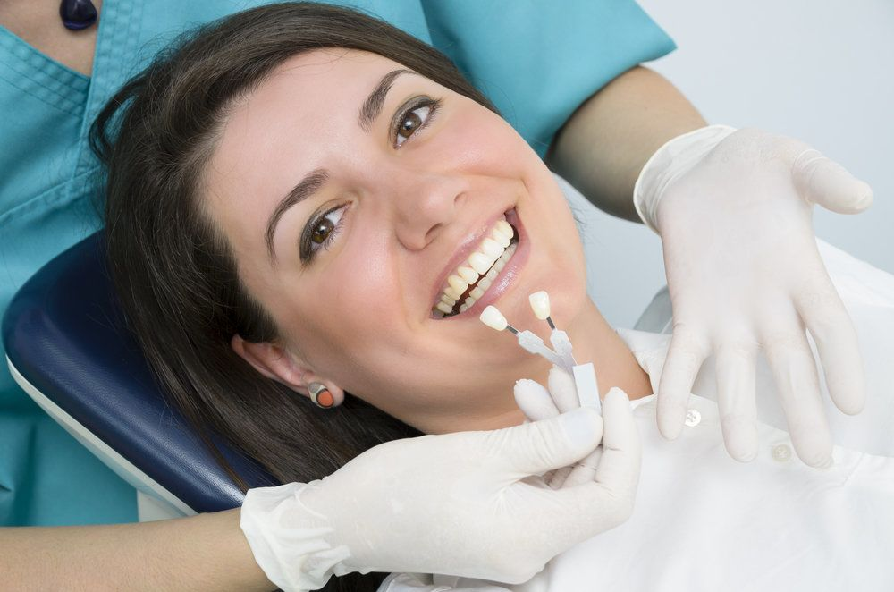 Smiling dental patient with shade samples near her teeth