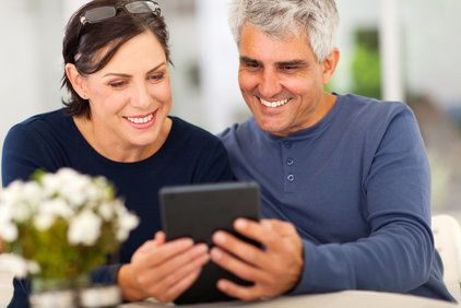 middle aged couple reading emails on tablet computer