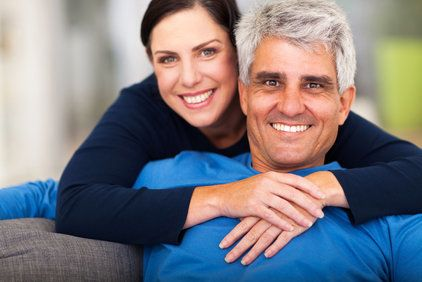 Happy, loving middle aged couple relaxing at home
