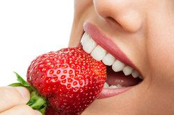 Up-close shot of woman with excellent teeth eating a strawberry.