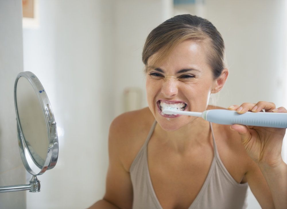 Female looks into mirror while using an electric toothbrush