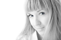Blond woman with blunt bangs smiling coyly
