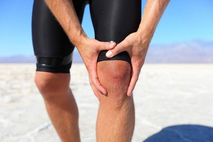 Man in spandex shorts on beach holding knee in pain