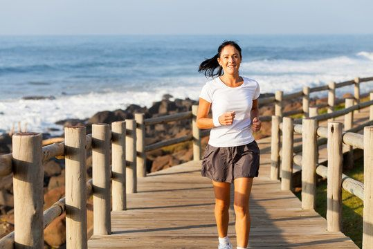 woman running along a beach boardwalk