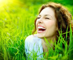 Laughing woman laying in grassy field