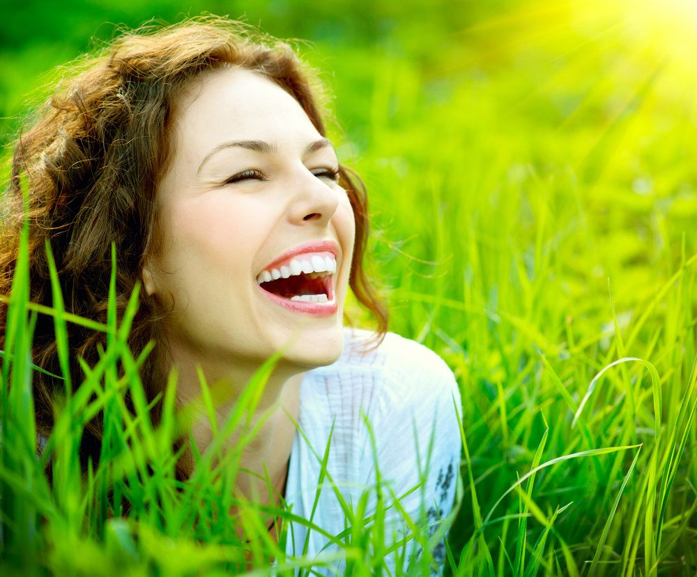 Woman with beautiful teeth laughing in the grass.