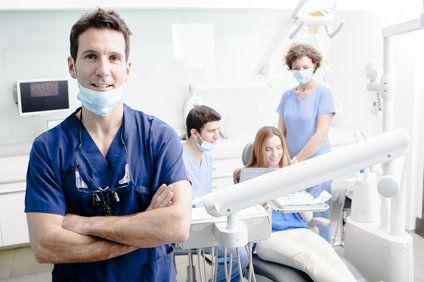 Oral surgeon and staff with patient