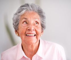 An elderly woman with short, dark-gray hair looks up to the right while smiling curiously.