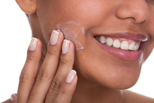 Smiling woman applying cosmetic cream to her cheek.