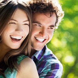 An attractive man and woman smiling while standing outside.