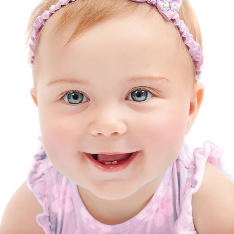 A little baby girl, dressed in pink and smiling sweetly
