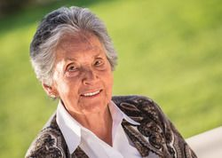 Smiling elderly woman posing in park