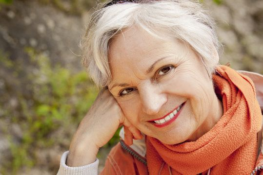 A woman with short, white hair wearing an orange scarf poses in front of a rock covered in moss.