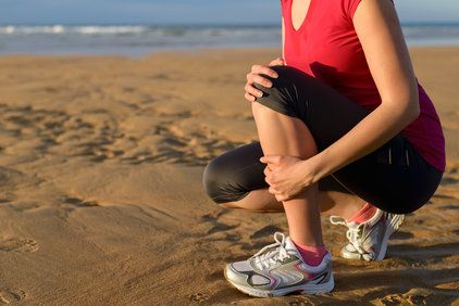 Kneeling female runner holding shin on beach