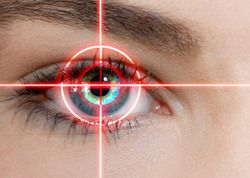 A woman's eye highlighted by a red digital target