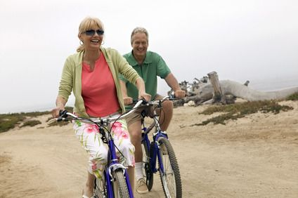 Laughing couple riding their bikes on the sand