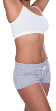 Slim woman in white sports bra and gray shorts holding arms above head