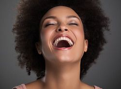 Woman laughing with head tilted back.