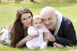 Bald man and brunette woman holding small baby in flower field