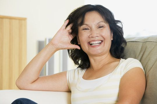 A middle-aged woman with black hair sits happily on her couch.