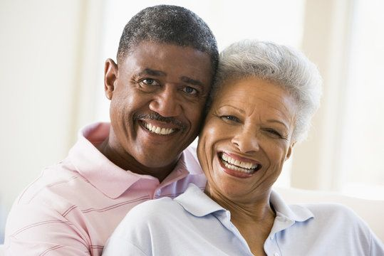 An elderly black couple smiles happily, wearing pastel shirts.