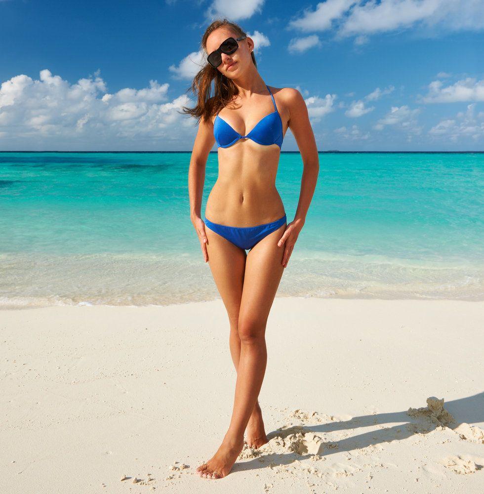 A woman on the beach in a blue bikini