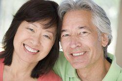 Un couple d'âge moyen asiatique souriant brillamment.
