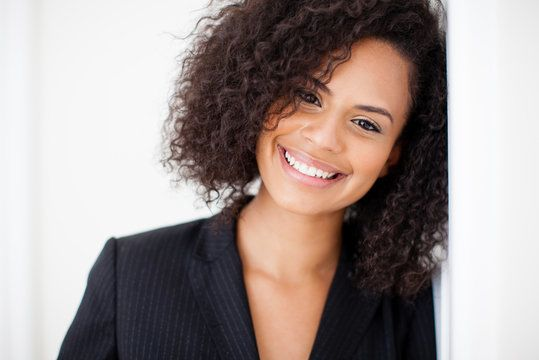 Smiling African American woman with curly hair wearing blazer