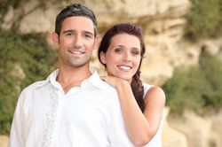 An attractive young couple standing in front of rocks.