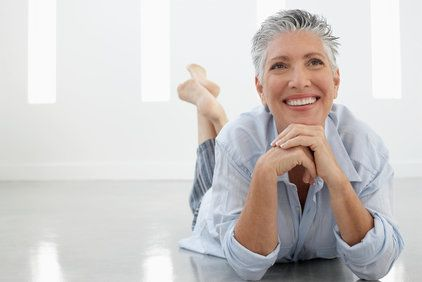 Smiling middle-aged woman lying on stomach with hands under chin