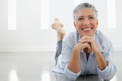 Older woman lying on the floor, showing off her healthy teeth and gums by smiling broadly