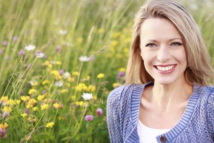 Smiling blond woman in blue sweater sitting in field of flowers