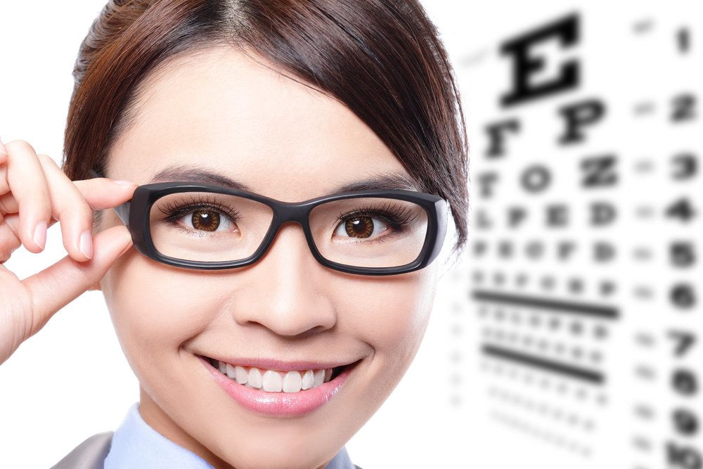 A woman wearing glasses in front of an eye chart