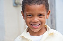 A sweet little boy smiles showing a full set of white baby teeth.