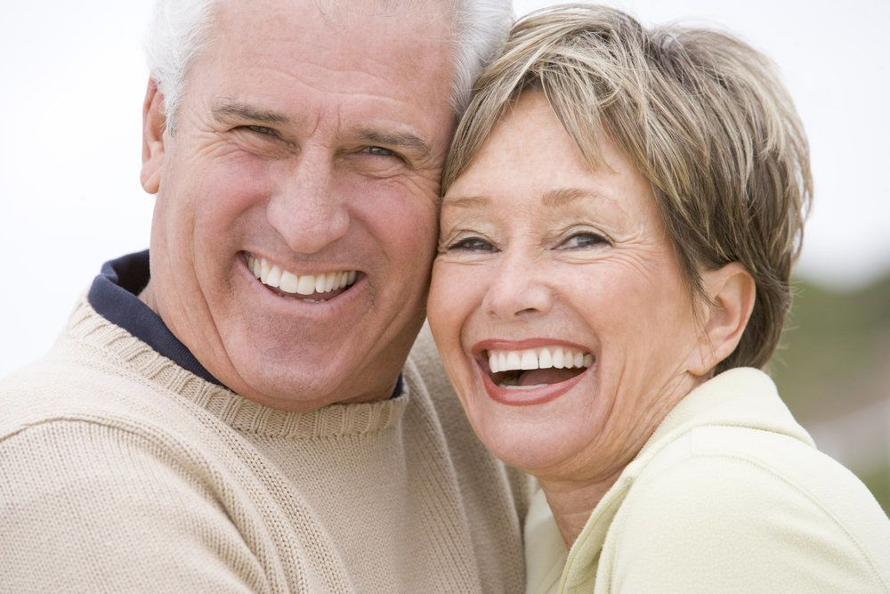 Older male and female with healthy and attractive smiles