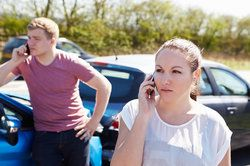 Young drivers make a call after an accident