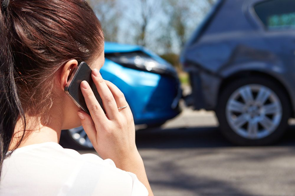 Teenager on the phone at the scene of an auto accident