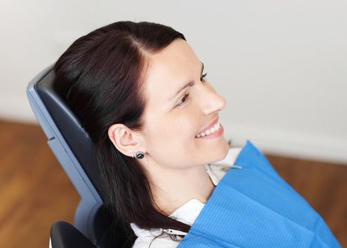 Relaxed, smiling woman reclining in dental exam chair