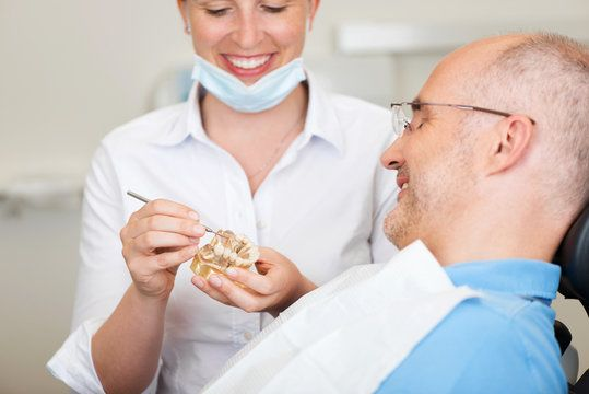 A dentist showing a patient a wax-up