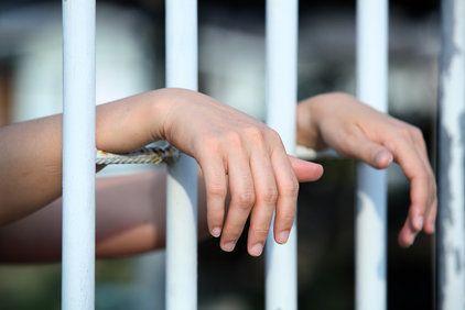 Prisoner resting hands on bars of cell door