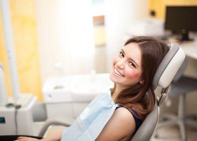 Brunette girl smiling in the dentist's chair