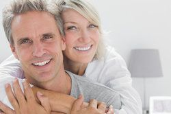 Affectionate couple smiling at camera at home