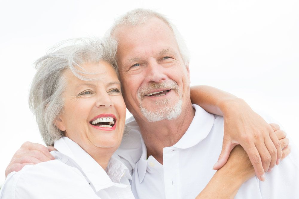 An older couple with full, healthy smiles