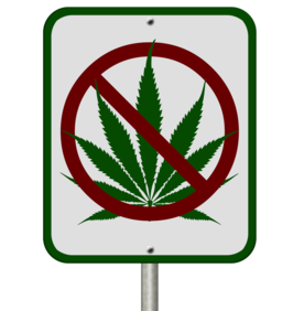 Road sign with marijuana leaf covered by