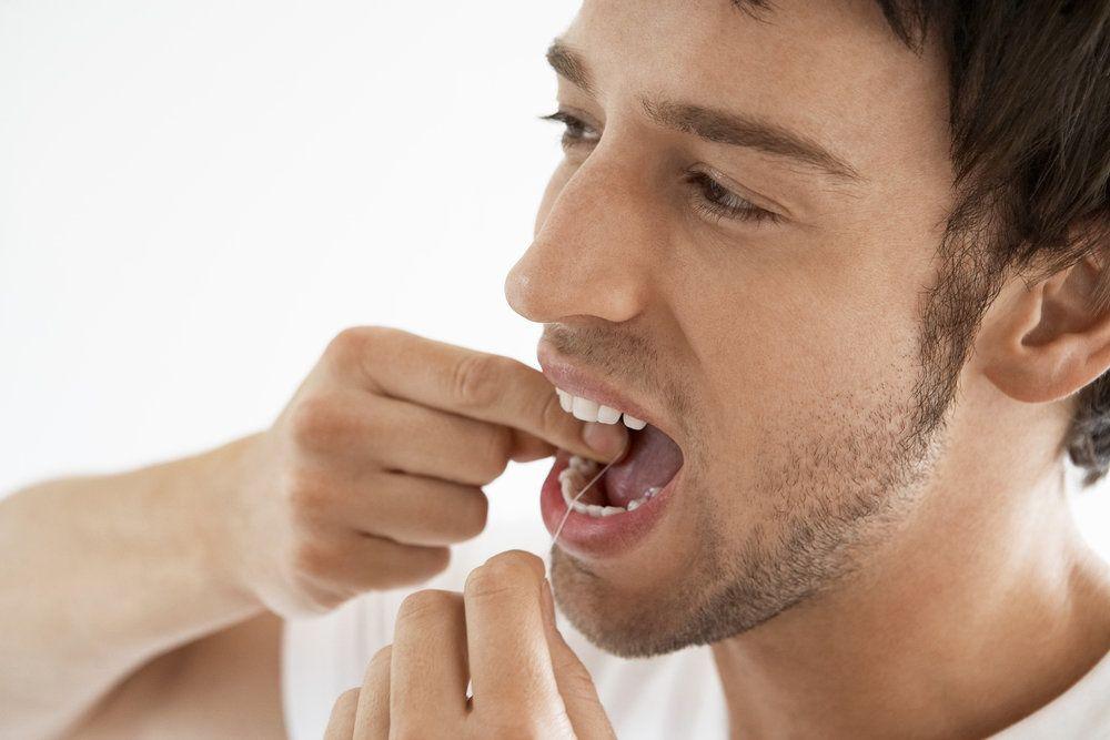 Male flossing his teeth