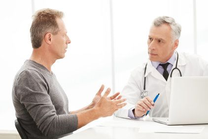 Middle-aged Caucasian man speaking animatedly with his doctor