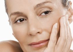 Middle-aged woman with head resting in hand, looking content with her soft facial skin after JUVÉDERM® and Restylane® injections
